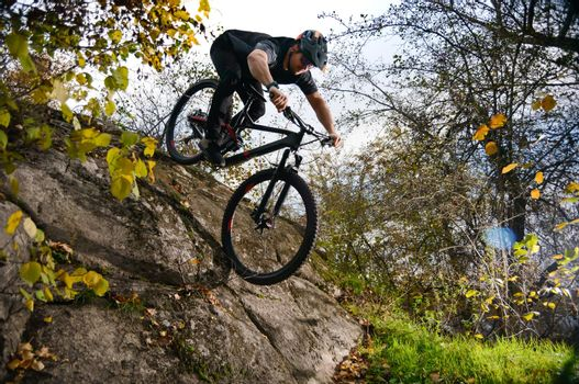 Professional Cyclist Riding Mountain Bike Down the Hill. Extreme Sport and Enduro Biking Concept.