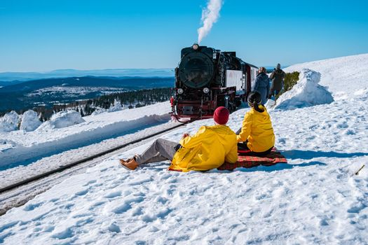 couple men and woman hiking in the Harz national park Germany, Steam train on the way to Brocken through the winter landscape, Famous steam train through the winter mountain. Brocken, Harz Germany