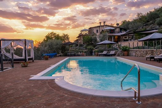 Luxury country house with swimming pool in Italy. Pool and old farm house during sunset central Italy