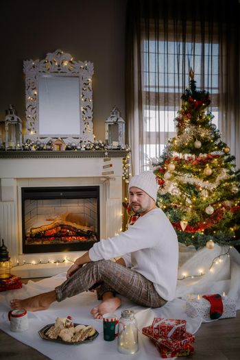 Cute, young guy mid age by fireplace with a Christmas tree,Family sitting on a floor. men near christmas tree with candle lights