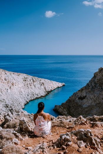 Crete Greece Seitan Limania beach with huge cliff by the blue ocean of the Island of Crete in Greece, Seitan limania beach on Crete, Greece. Europe young woman mid age asian looking out over ocean during vacation
