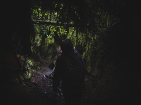 Friends exploring a cave in the forest.