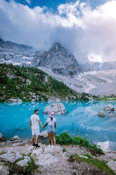 Couple visit the blue green lake in the Italian Dolomites,Beautiful Lake Sorapis Lago di Sorapis in Dolomites, popular travel destination in Italy