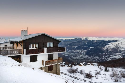 Saint Lary Soulan, France - December 26, 2020: mountain chalet in a snowy ski resort on a winter evening during the holiday season