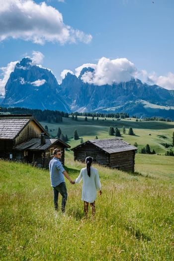 Alpe di Siusi - Seiser Alm with Sassolungo - Langkofel mountain group in background at sunset. Yellow spring flowers and wooden chalets in Dolomites, Trentino Alto Adige, South Tyrol, Italy, Europe. Summer weather with dark clouds rain, couple men and woman on vacation in the Dolomites Italy