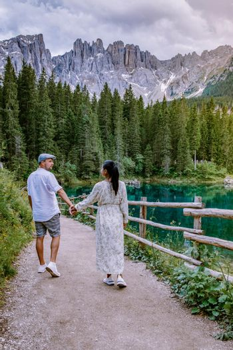 couple visit hte bleu lake in the dolomites Italy, Carezza lake Lago di Carezza, Karersee with Mount Latemar, Bolzano province, South tyrol, Italy. Landscape of Lake Carezza or Karersee and Dolomites in background, Nova Levante, Bolzano, Italy. Europe