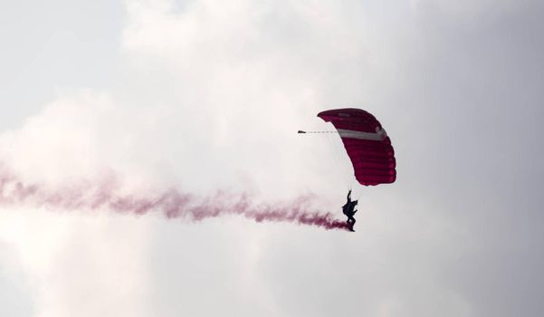 silhouette parachute stunt unfocused and blurry while gliding in the air with red smoke trail during an air exhibition in Singapore