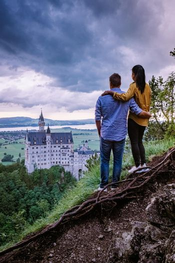 couple men and woman visit Neuschwanstein Castle. Beautiful view of world-famous Neuschwanstein Castle, the nineteenth-century Romanesque Revival palace built for King Ludwig II on a rugged cliff near Fussen, southwest Bavaria, Germany
