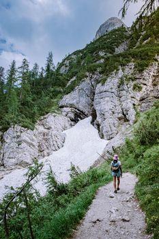 woman hiking to blue green lake in the Italian Dolomites,Beautiful Lake Sorapis Lago di Sorapis in Dolomites, popular travel destination in Italy