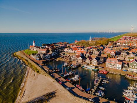 Urk lighthouse with old harbor during sunset, Urk is a small village by the lake Ijsselmeer in the Netherlands Flevoland area. beach and harbor of Urk November 2020