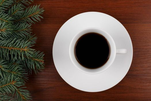 Close up of a white ceramic coffee cup with a saucer on dark shiny wooden table decorated with Christmas tree from the left side. The concept of New Year and Christmas