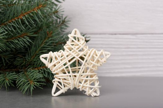 White Christmas star with Christmas tree against white wooden background. Concept of New Year, Christmas and winter holiday season