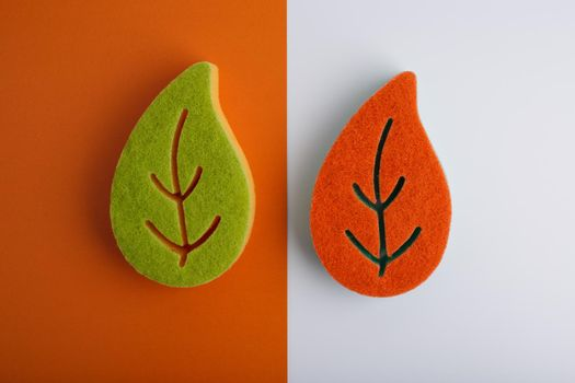 Top view of colorful leaf shaped sponges for home, kitchen, bathroom and and dishes cleaning on orange and white background