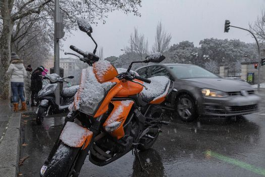Madrid, Spain - January 07, 2021: A parked orange motorbike, covered in snow, and traffic on Avenida de Menedez Pelayo, in the middle of a wave of polar cold.
