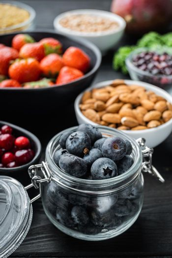Superfoods dieting concept, on black wooden background