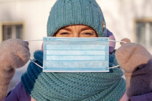 A girl in a jacket and hat in the winter on the street puts on a protective medical mask during the coronovirus pandemic. A girl holds a medical mask in her hands in the cold.