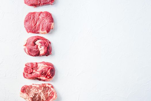 Raw set of alternative beef cuts Chuck eye roll, top blade, rump steak. Organic meat. White textured background.Top view with space for text