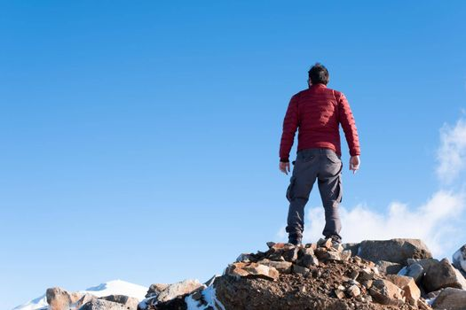It depicts a man with red jacket standing on the mountain success concept