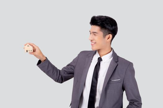 Young asian business man holding the home symbol of saving for future, insurance agent and credit, ownership house, debt and loan of finance, purchase home and refinance, investment real property.