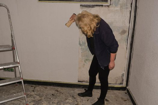 Woman glues wallpaper on the wall