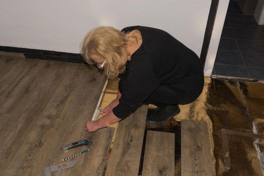 Woman is laying laminate floor. repair concept