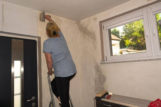 Woman in casual clothes, rolls of wallpaper on a wall.