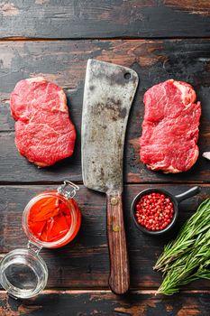 Rump steak organic meat cut, raw marbled beef steak, with old butcher knife cleaver, and seasonings On dark wooden rustic table, top view