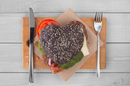 Heart shape love black hamburger, burger fast food concept, Valentines day surprise dinner, wooden background, top view flat lay
