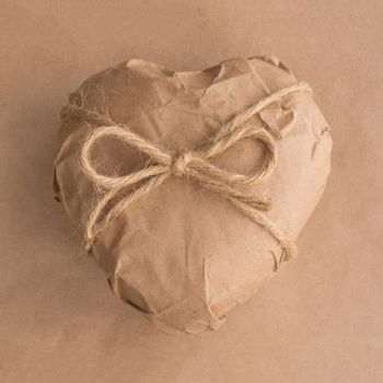 Heart gift in brown Wrapping craft Paper tied with rope bow on background Valentine day surprise concept