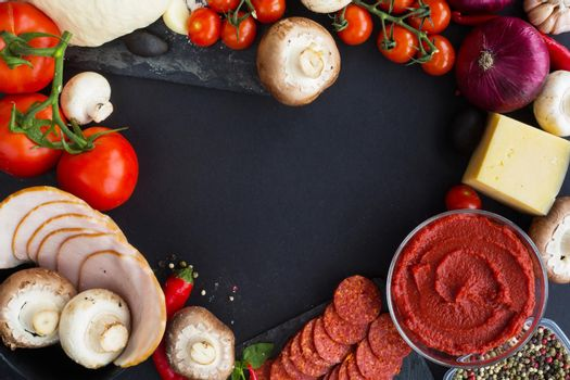 Raw dough for pizza with ingredients and spices on black table background in heart shape love food of Valentines day concept