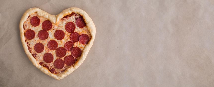 Pizza heart shaped with pepperoni on craft brown paper background. Concept of romantic love for Valentines Day . Love food, Copy space for text