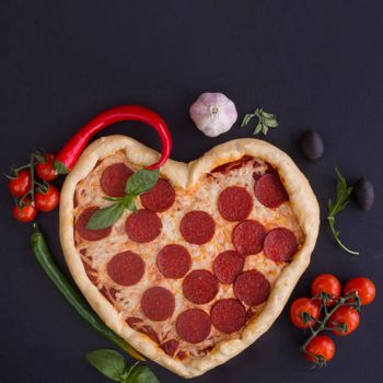 Pizza heart shaped with pepperoni with ingredients on black background. Concept of romantic love for Valentines Day . Love food