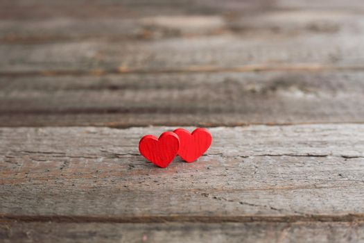 Small red hearts on wooden background with copy space