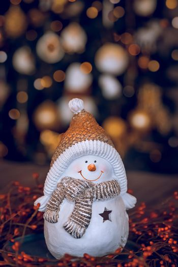 Happy Winter Holidays at Home. Nice Little Snowman Candlestick on the Table over Decorated Glowing Christmas Tree Background. Festive Still Life with Bokeh