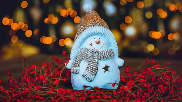 Beautiful Christmas Home Decoration. Cute Little Snowman Toy Standing in the Red Berries Wreath on the Table over Glowing Xmas Tree Bokeh Lights Background. Happy New Year