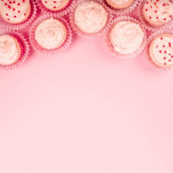 Valentine day love cupcakes decorated with cream and hearts on pink background with copy space for text