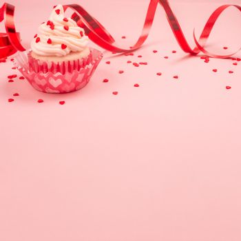 Valentine day love cupcake decorated with cream and hearts on pink background with copy space for text