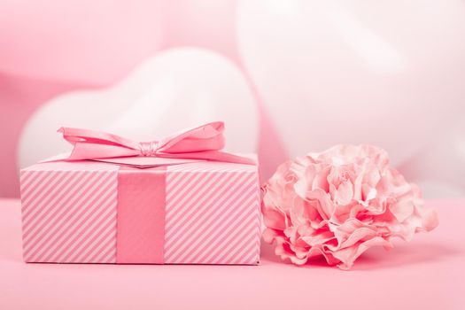 Valentine Day gift in a box wrapped in striped paper and tied with silk ribbon bow and heart shaped greeting card and rose flower on pink background with copy space for text