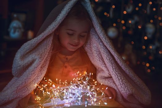 Portrait of a Cute Little Baby Covered with a Blanket. Enjoying Magic Lights of Christmas Tree Decoration. Happy Winter Holidays at Home.