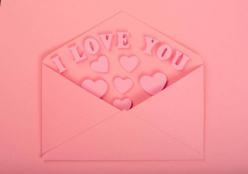 Pink love letter and wooden hearts painted I love you letters on pink background