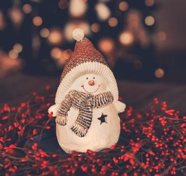 Beautiful Christmas Decoration. Cute Little Snowman Toy Standing in the Red Christmas Wreath on the Table over Glowing Xmas Tree Background Bokeh. Festive Winter Holidays Still Life. Vintage Style Photo.