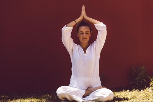 Pretty Woman Dressed in Clean White Clothes Sitting in Lotus Posture with Closed Eyes and Meditating. Inner Peace