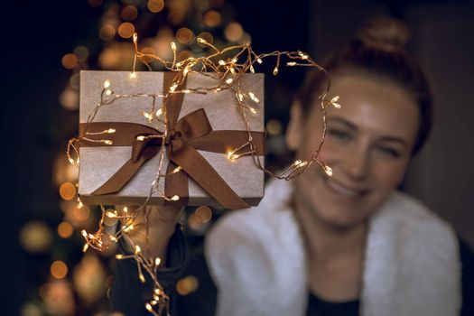 Selective Focus Image. Pretty Happy Young Woman Got a Present. Beautiful Golden Gift Box Over Decorated Christmas Tree Background. People Celebrating Winter Holidays at Home. Christmas Eve Joy. Happy New Year.