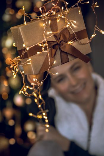 Selective Focus Image. Christmas Preparation at Home. Pretty Happy Young Woman Packing Presents. Beautiful Golden Gift Box Over Decorated Christmas Tree Bokeh Background. People Celebrating Winter Holidays. Christmas Eve Joy. New Year.