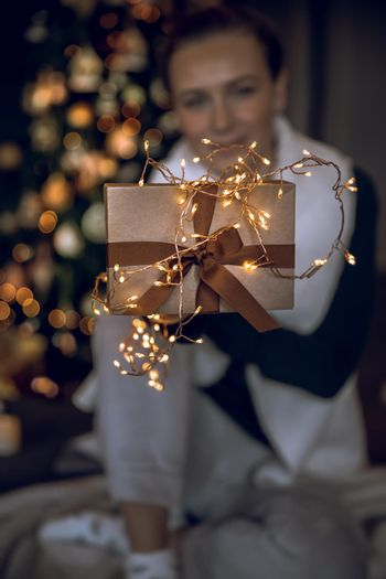 Pretty Girl Receiving Festive Gift from Santa. Stylish Golden Gift Box Decorated with Glowing Garland Lights. Cozy Christmas Party at Home.