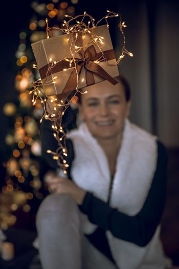 Beautiful Stylish Golden Gift Box Decorated with Glowing Christmas Lights in Women's Hands. Girl Spending Winter Holidays at Home. Preparing Decorations and Presents for a Party. Selective Focus Image. Merry Christmas and Happy New Year.