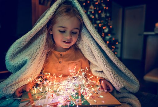 Cute Little Baby Under Plaid with Pleasure Reading Christmas Tale Book and Enjoying Beautiful Glowing Gift. Hygge. Christmas Eve at Home.
