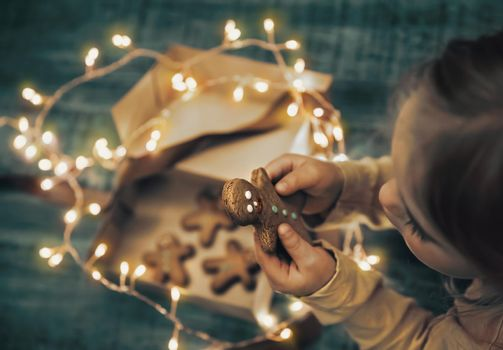 Child Received Gift Box with Christmas Cookies Decorated with Glowing Garland. Little Baby Eating Gingerbread. Happy Winter Holidays.
