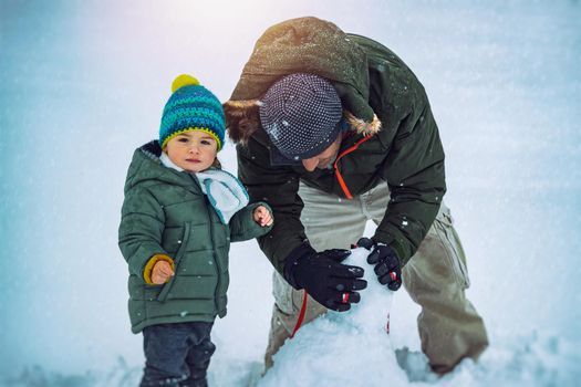 Cute Little Baby Boy with Father Having Fun Outdoors in Winter Time. With Pleasure Building Snowman. Enjoying Winter Holidays.