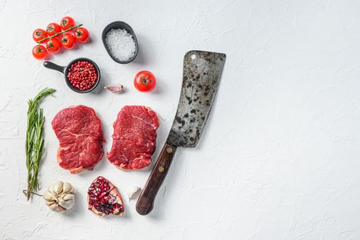 Raw rump steak, farm beef meat with seasonings, rosemary, garlic and butcher cleaver. White textured background. Top view with space for text.